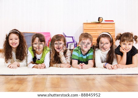 Group of laughing kids lying on floor - stock photo