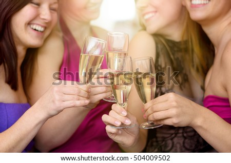 Group of laughing merry young women toasting together with flutes of champagne at a party as they celebrate a special occasion, close up view on their hands