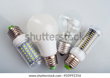 Group of light bulbs. Old generation bulb, Tungsten bulb, and white energy saving bulb - stock photo