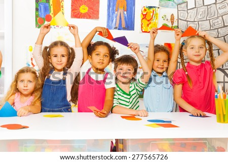 Group of little boys and girls sitting by the table holding color cardboard shapes in kindergarten room