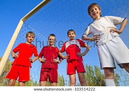 Group of Little Boys stay next to goal - stock photo