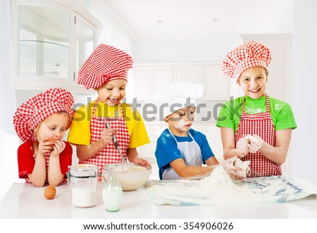 Group of little funny bakers at the kitchen - stock photo