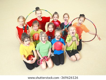 Group of little gymnasts in gym - stock photo