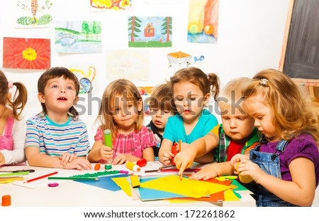Group of little kids painting with pencils and gluing with glue stick on art class in kindergarten - stock photo