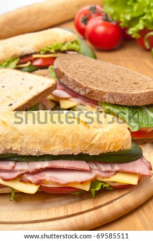 group of long baguette and toasted sandwiches with lettuce, vegetables, salami, ham and cheese on a cutting board and ingredients - stock photo