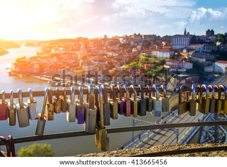 Group of love padlocks attached to a fence over beautiful Porto view