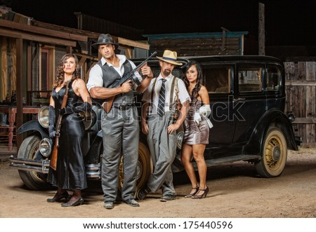 Group of male and female gangsters with guns - stock photo