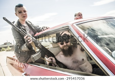 Group of male and female gangsters with guns Man and woman hold Kalashnikov assault rifle and drive inside retro red car on on city street Gangster wear black cowboy hat and circle sunglasses  - stock photo