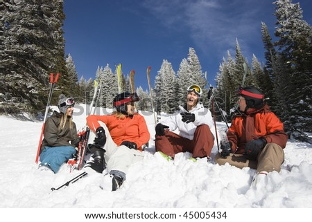 Group of male and female skiers sitting in the snow relaxing talking and smiling. Horizontal shot. - stock photo