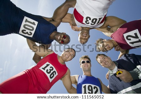 Group of male athletes with trainer forming a huddle against sky - stock photo