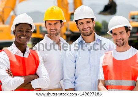 Group of male construction workers at a building site  - stock photo