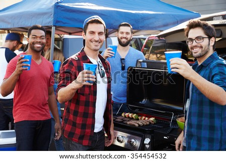 Group Of Male Sports Fans Tailgating In Stadium Car Park - stock photo