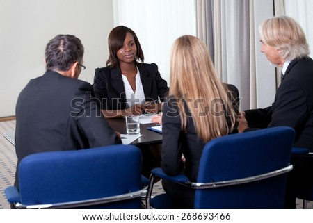 Group of managers interviewing pretty young female candidate for job at the office - stock photo