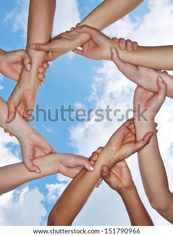 Group of many hands forming a chain under a sky - stock photo