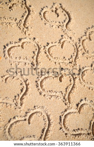 Group of many handwritten love heart symbol on sunny sandy beach background. Lovely holiday vacation greeting card. - stock photo