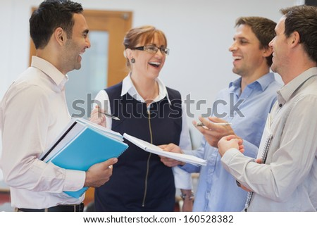 Group of mature students standing in classroom chatting and laughing - stock photo