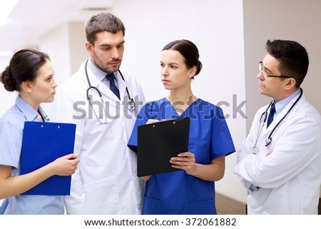 group of medics at hospital with clipboard - stock photo