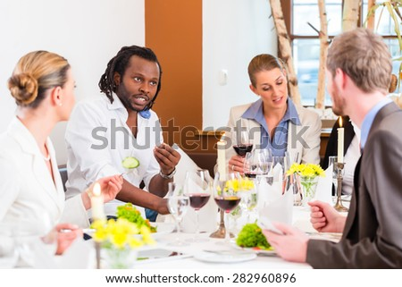 Group of men and women at business lunch in restaurant eating and drinking - stock photo
