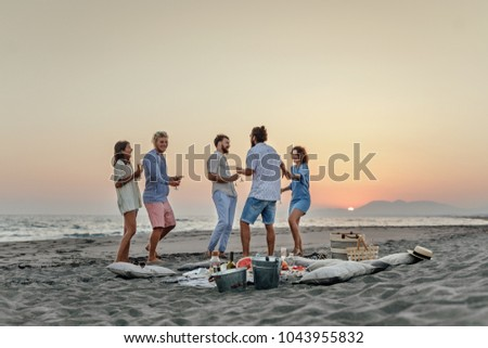 Group of men and women having fun and dancing on beach party.