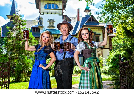 Group of men and women in traditional german Tracht with beer - stock photo