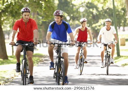Group Of Men On Cycle Ride Through Park - stock photo