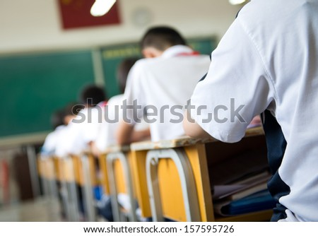 group of middle school students studying in classroom - stock photo