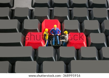 group of miniature engineers (people model) fixing computer and machine - stock photo