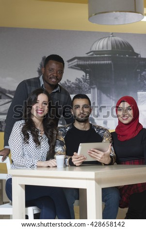 Group of mixed-race students chatting and smiling at university canteen on a break - stock photo