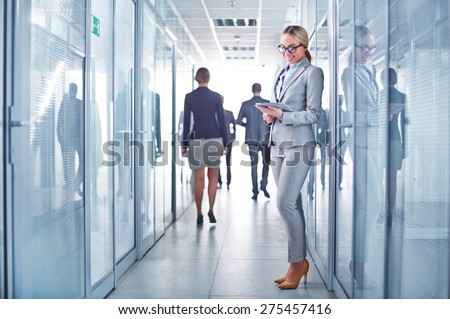Group of modern business people in corridor of office building