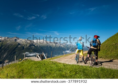 group of mountain bikers riding an enduro trail in the austrian alps in salzburg near kaprun with epic peak view - stock photo