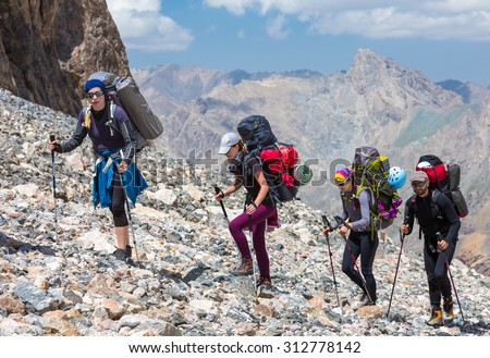 Group of Mountaineer Walking on Deserted Rocky Terrain Five Members Team Sport Clothing Going Heavy Load Backpacks Climbing Gear Up  Mountain Peaks Blue Sky Majestic Summits Shining Sun Background - stock photo