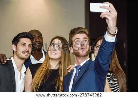 Group of multi-ethnic businesspeople taking a picture themselves with a mobile phone after a business meeting