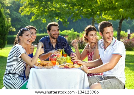 Group of multi ethnic friends having picnic. Group of adult family members laughing heartily as they look over their shoulders at something off screen to the right - stock photo