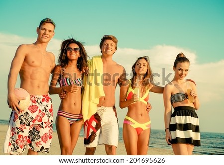 Group of multi ethnic friends walking on a beach
