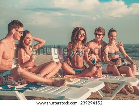 Group of multi ethnic friends with drinks relaxing on a beach - stock photo