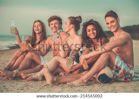 Group of multi ethnic friends with drinks sitting on a beach - stock photo