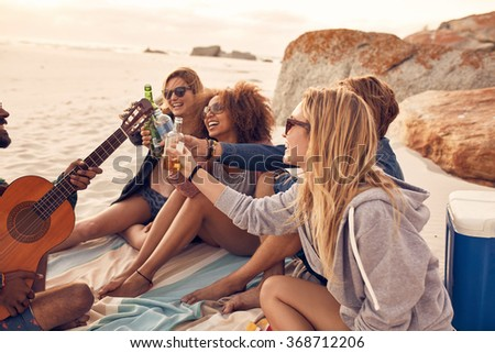 Group of multi-ethnic young people toasting beers on the beach. Group of friends spending time together at the beach with a guitar and a few drinks. - stock photo