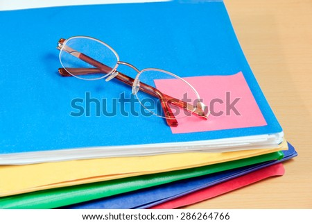 Group of multicolored office folders and glasses on table - stock photo