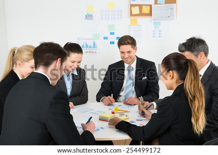 Group Of Multiethnic Businesspeople Analyzing Graph In Office - stock photo