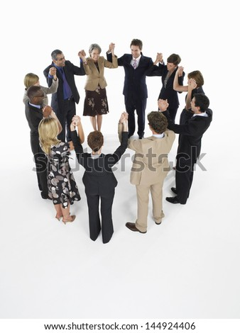 Group of multiethnic businesspeople holding hands in a circle against white background - stock photo