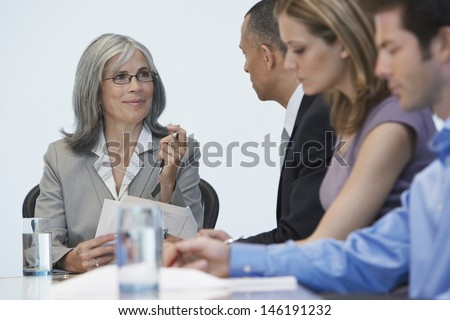 Group of multiethnic businesspeople sitting at conference table - stock photo
