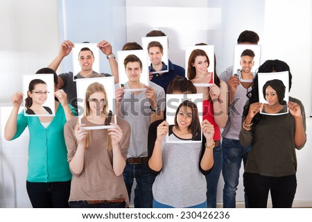 Group of multiethnic college students holding photographs in front of faces at classroom - stock photo