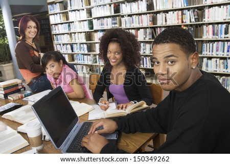 Group of multiethnic college students studying together in library - stock photo