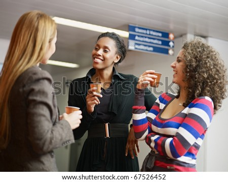 group of multiethnic female colleagues drinking coffee and tea. Horizontal shape, waist up