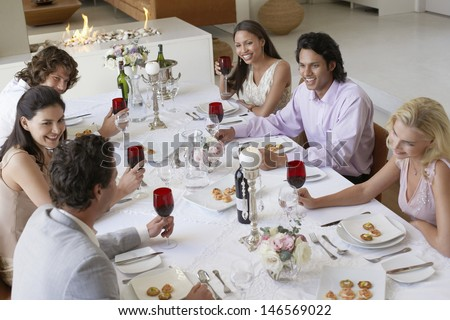 Group of multiethnic friends drinking and socialising at dinner party - stock photo