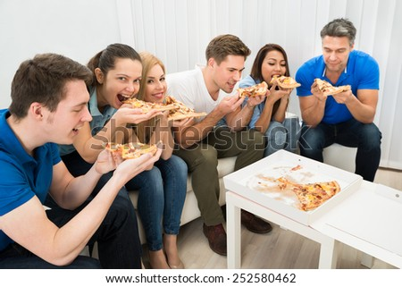 Group Of Multiethnic Friends Eating Pizza Together - stock photo