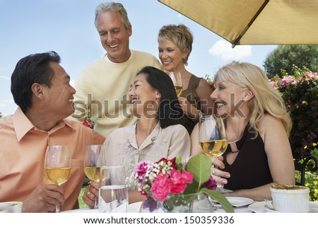 Group of multiethnic friends enjoying drinks at dinner table outdoors - stock photo