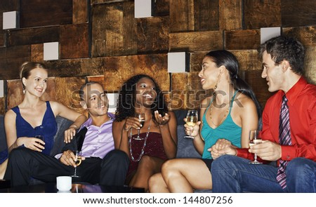 Group of multiethnic friends sitting on couch with drinks in bar - stock photo