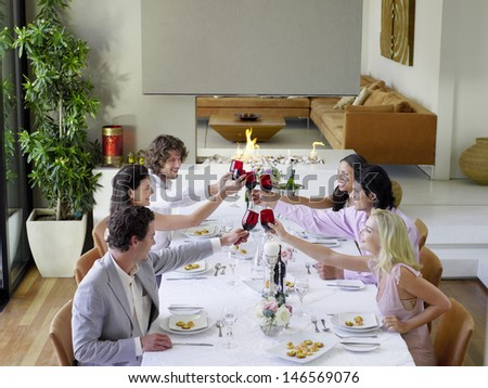 Group of multiethnic friends toasting wineglasses across table at dinner party - stock photo