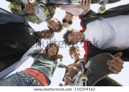 Group of multiethnic friends with skateboards forming circle from below - stock photo